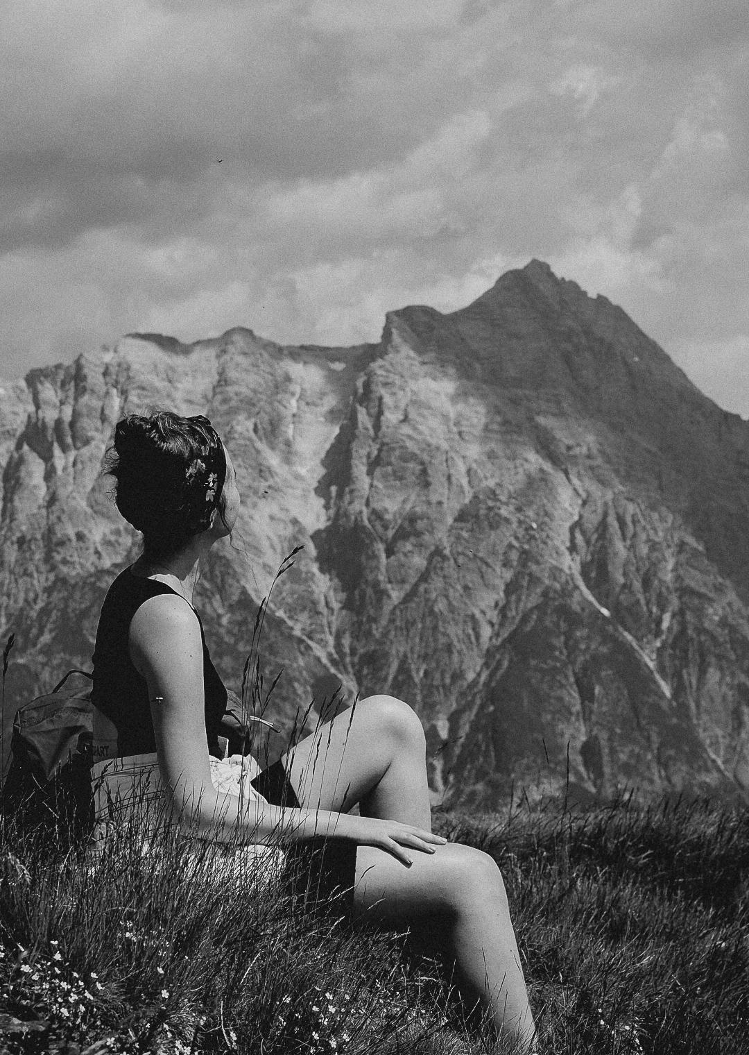 Sommerurlaub in Salzburg auf den Bergen. Im Hintergrund sind die Bergspitzen zu sehen und im Vordergrund sitze ich in einer Wiese und blicke zu den Bergen.