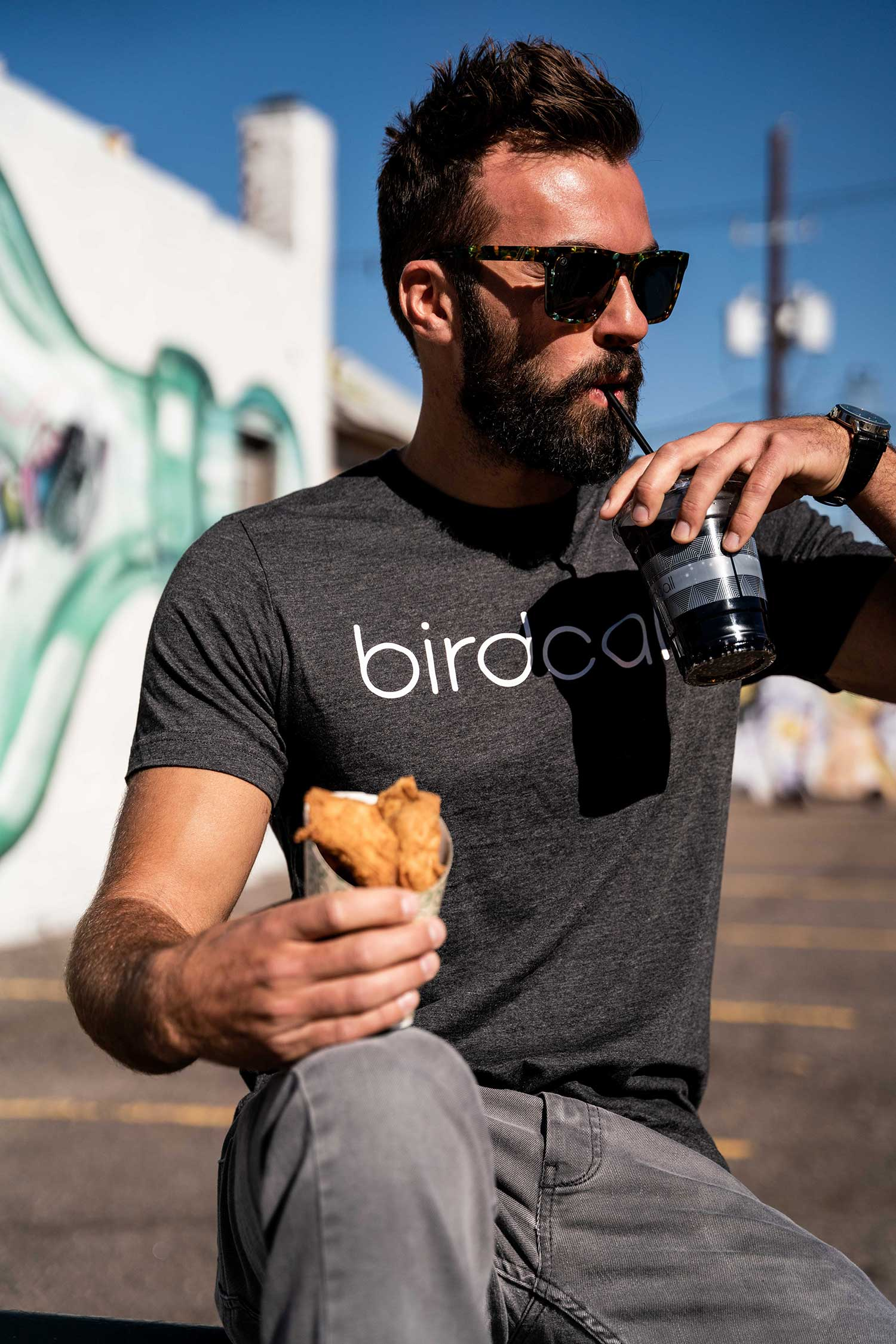 Man in Birdcall t-shirt eating