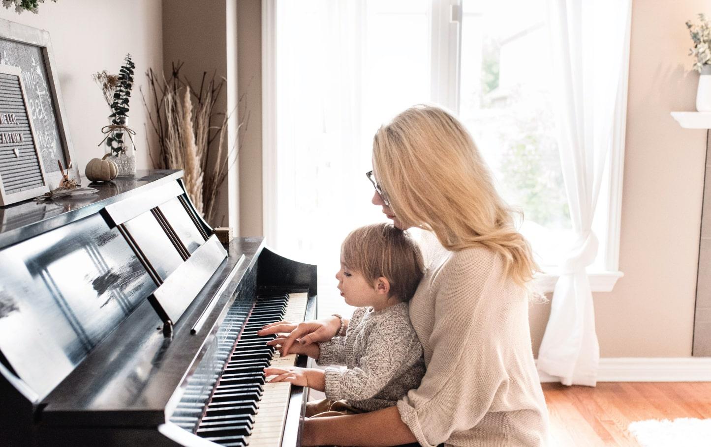 femme apprenant le piano avec son fils, sur un piano acoustique noir