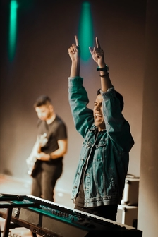 Jeune homme sur scène au pianoles bras en l'air