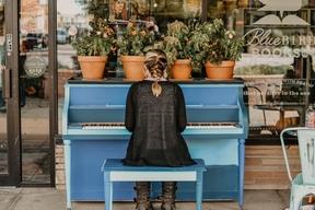 Jeune femme de dos assise devant son piano