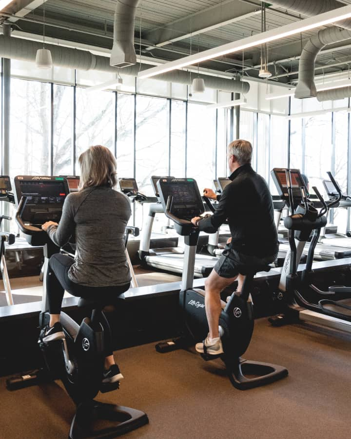 Medium shot of a middle-aged couple exercising on stationary bikes in a gym.