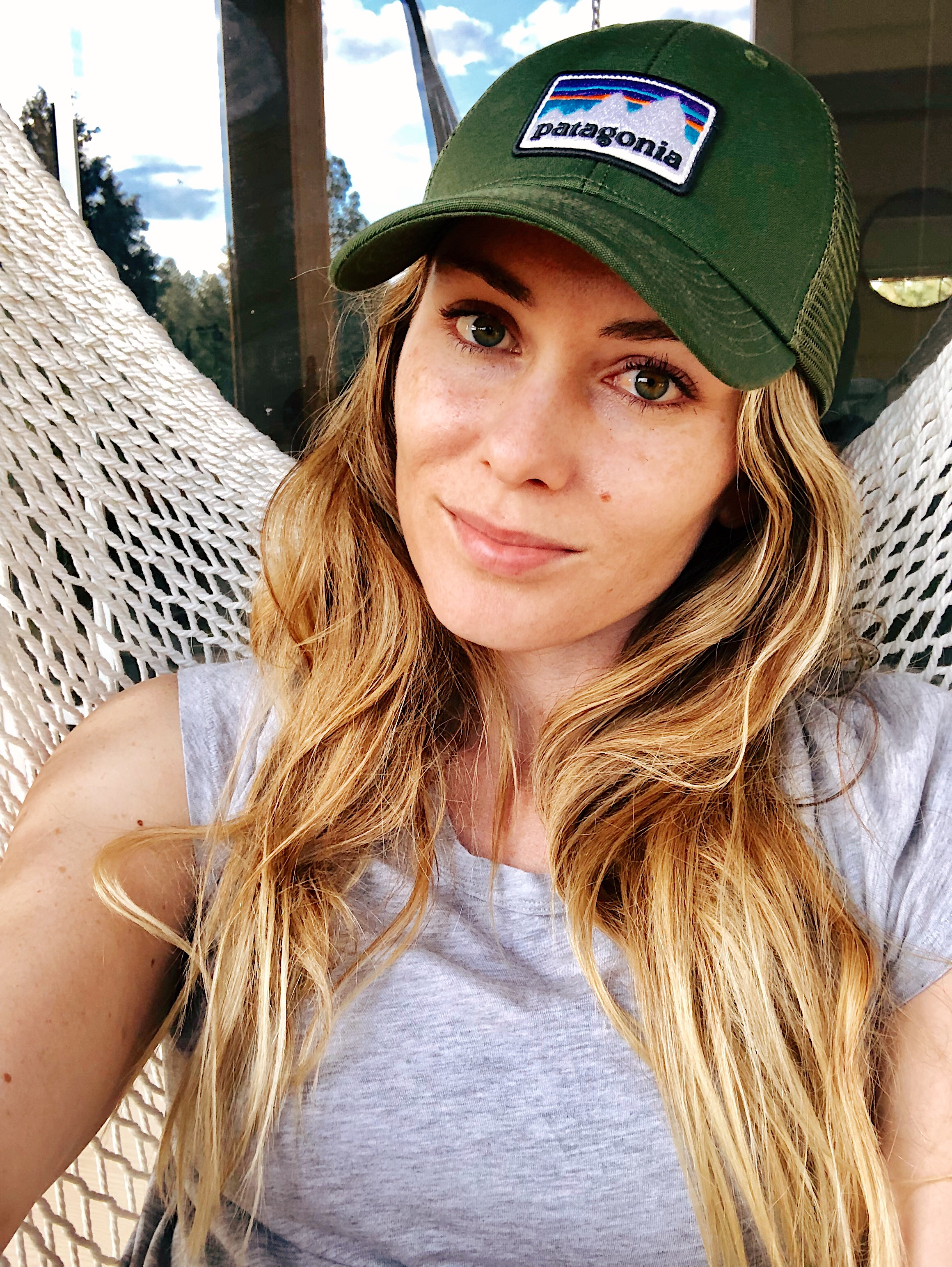 A portrait of me, Juliana Linder. I'm wearing a green Patagonia hat, a grey shirt, looking directly into the camera with a closed smile.