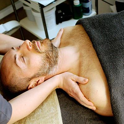 Ein Mann liegt auf dem Rücken und lässt sich die Schultern massieren