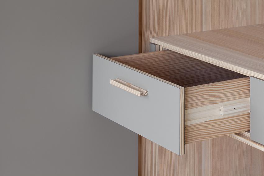 Geöffnete Schublade eines Kleiderschrankes aus Massivholz.