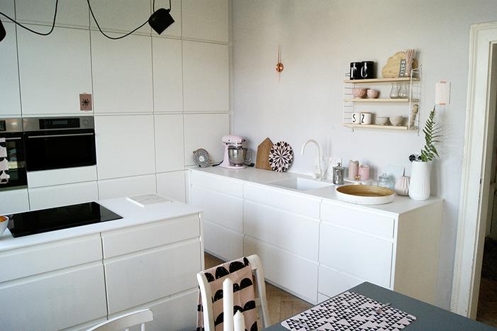 Küche mit weiss lackierten grifflosen Möbeln.