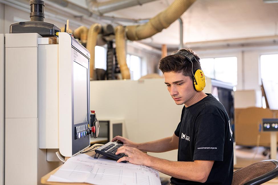 Ein Mitarbeiter der Schreinerei Angel richtet eine Maschine ein