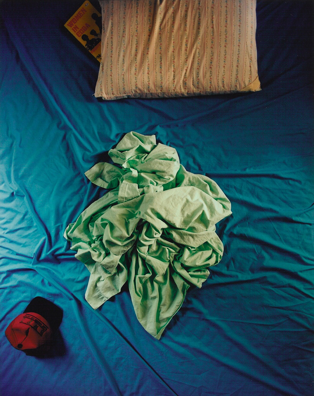 A bird's eye view of a crumpled sea-foam green sheet, on top of a bed encased in a wrinkled blue sheet. A red hat sits on the beds next to the sheet, alongside a patterned pillow with a book partially tucked under its left edge.