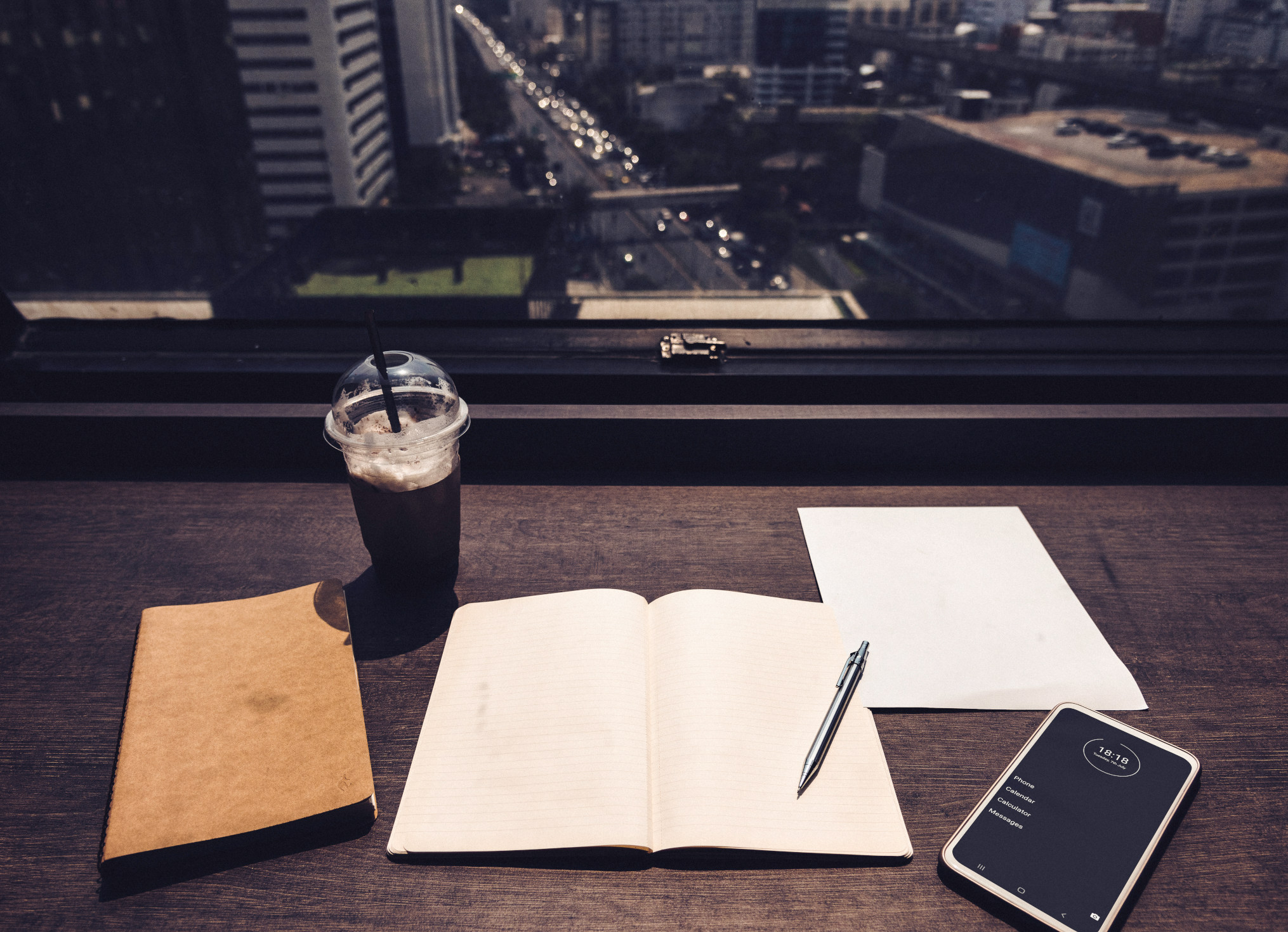 For better focus - minimalist phone on a desk and workbook - will reduce your screentime