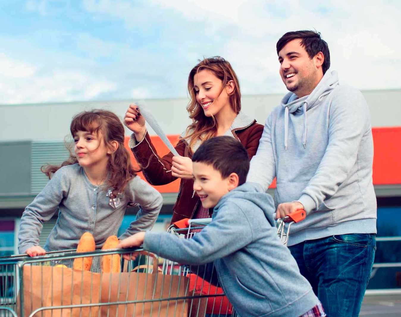 Family with two children pushing shopping cart full of grocery bags