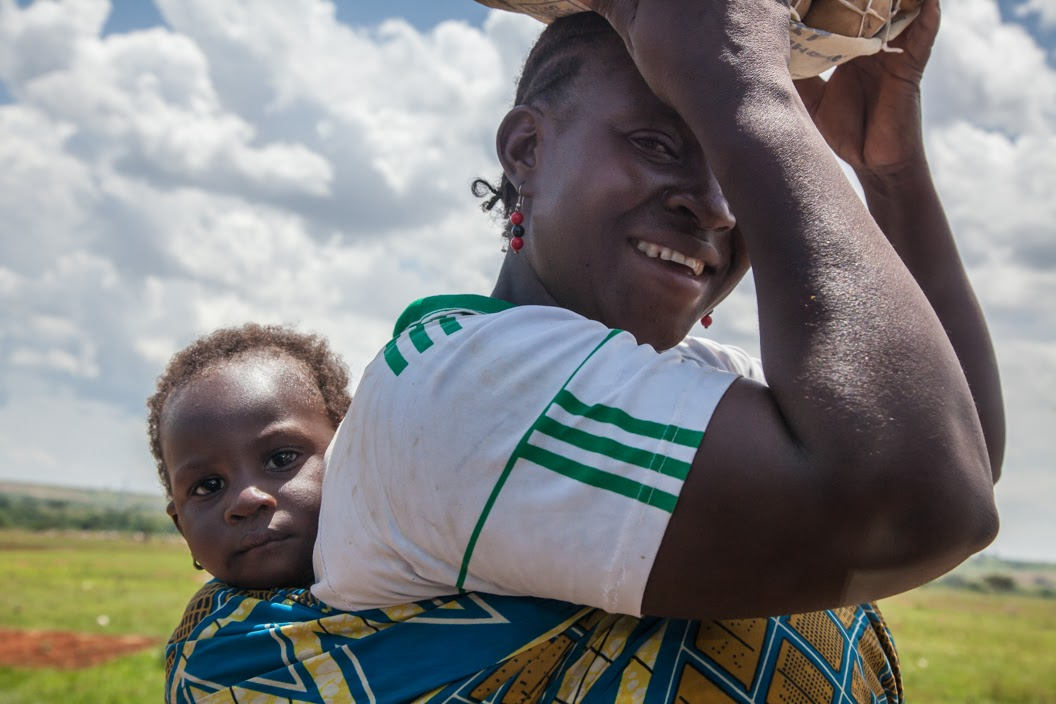 African woman smiling with baby on her back
