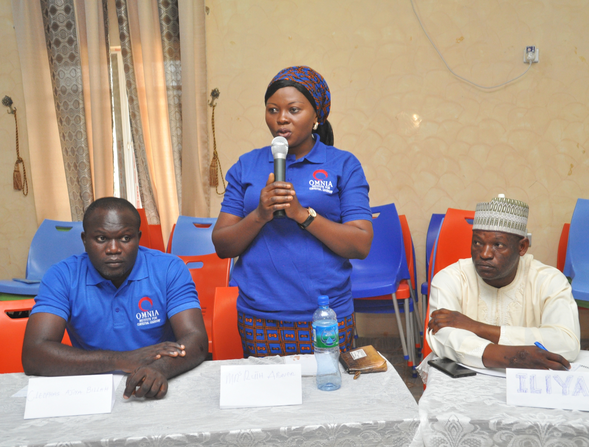 Woman speaking into microphone at an Interfaith Peacemaker Team meeting in Nigeria