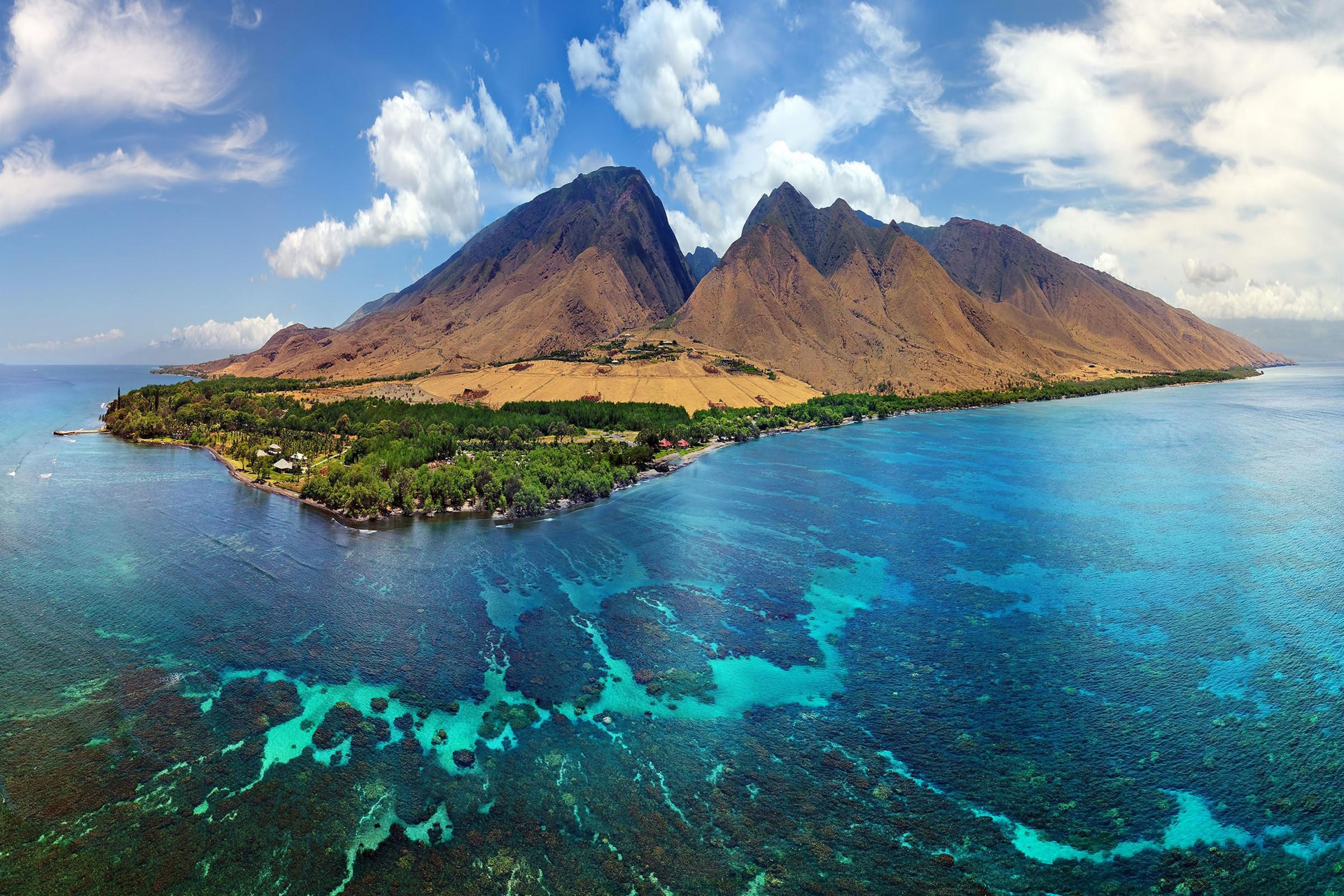 A tropical, mountainous island surrounded by clear turquoise waters with visible coral reefs below the surface