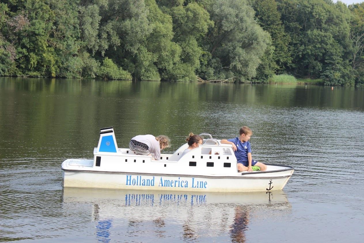 ילדים בסירה חשמלית באגם ביער אמסטרדם