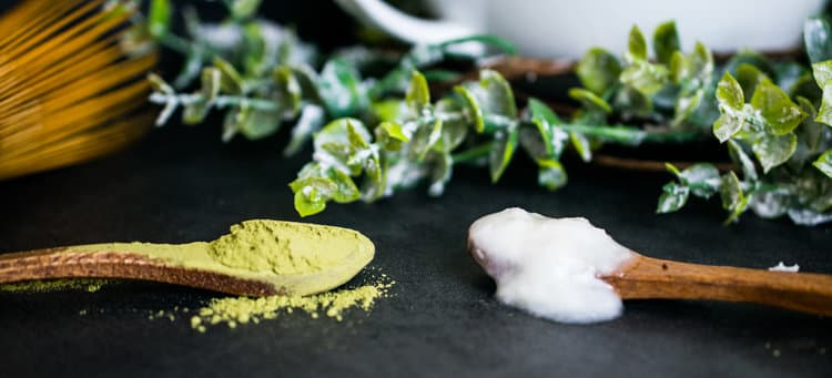 Wooden spoonfuls of matcha powder and coconut butter
