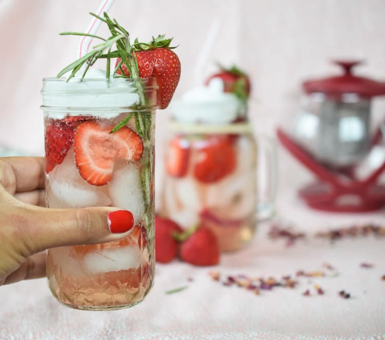 Holding a glass of rose float with strawberry and rosemary