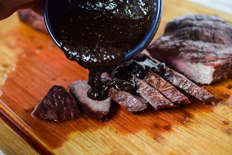 Pouring chocolate steak sauce on sliced steak