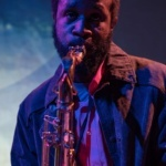 Headshot of Jerome Ellis playing an instrument with a blue background