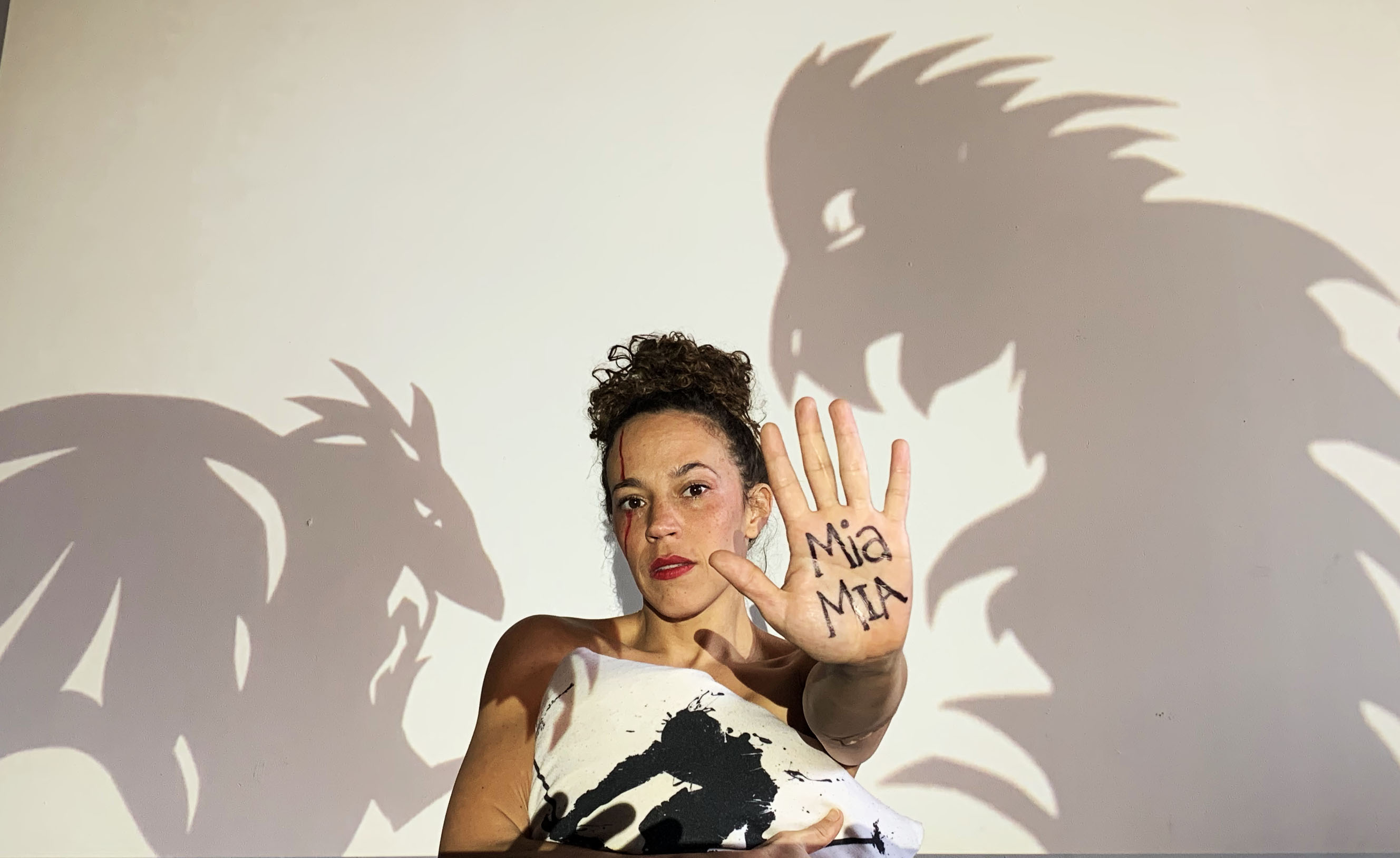 Charlotte. An actress stands in front of a white wall with shadow dragons on the wall. She extends her hand forward with writing on it using black paint. She is wearing a white top.