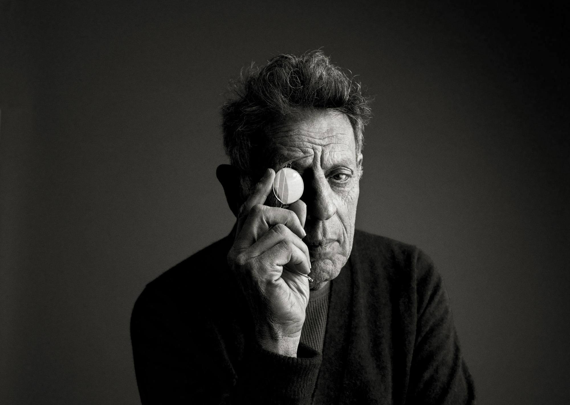 Philip Glass headshot in black and white with his hand held in front of one eye as if looking through a magnifying glass.