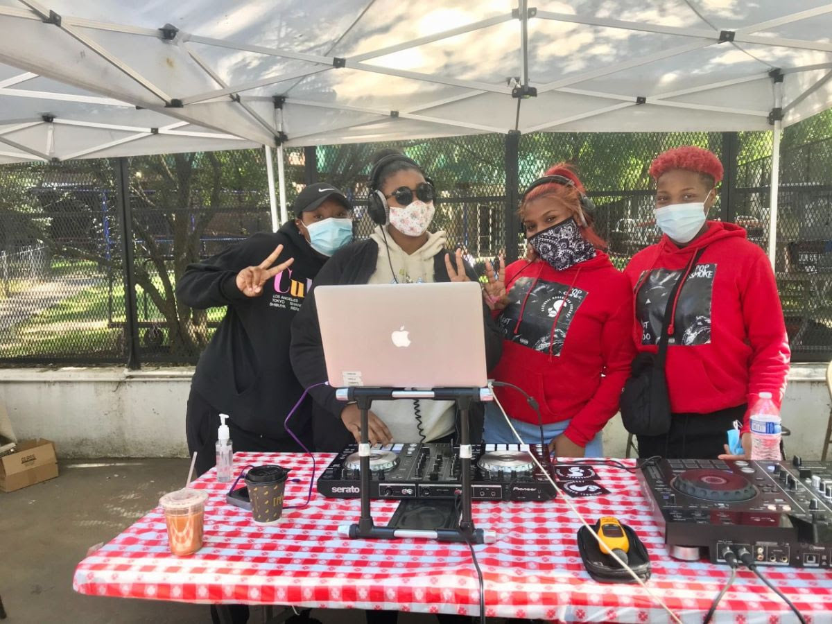 Young members of the Lower East Side Girls Club standing behind a computer setup like a DJ booth wearing masks and posing for the camera