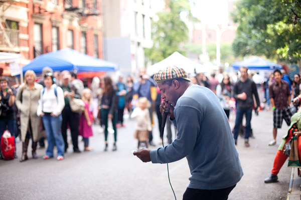 Kid Lucky performing into a microphone in a colorful hat for an audience in the street out of focus