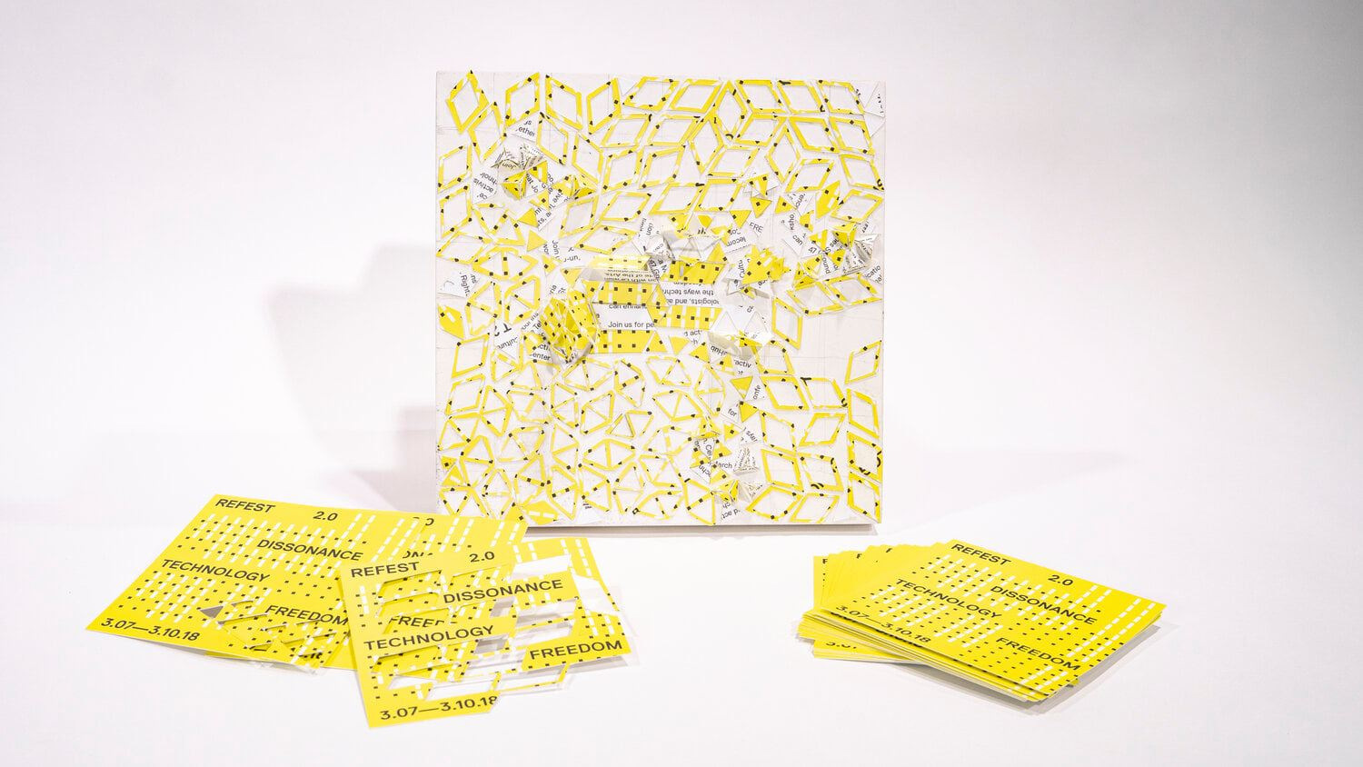 yellow postcards on a white surface and a small square where the cards have been torn and pasted into a collage