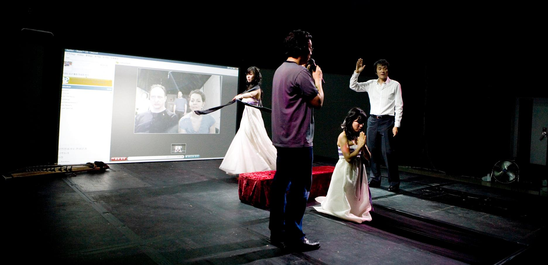 performers stand in a space wearing white and red in front of a projection screen with video on it