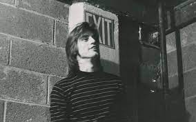 archival photo of playwright sam shepard in black and white standing in la mama in front of an exit sign and cinder block wall in black and white