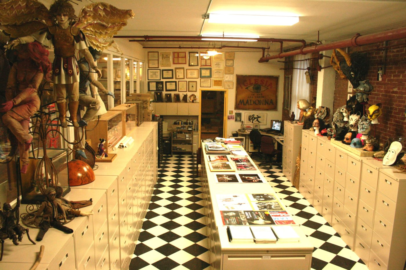 photo of the la mama archive office lined with file cabinets and puppets hanging above them on the walls with framed awards