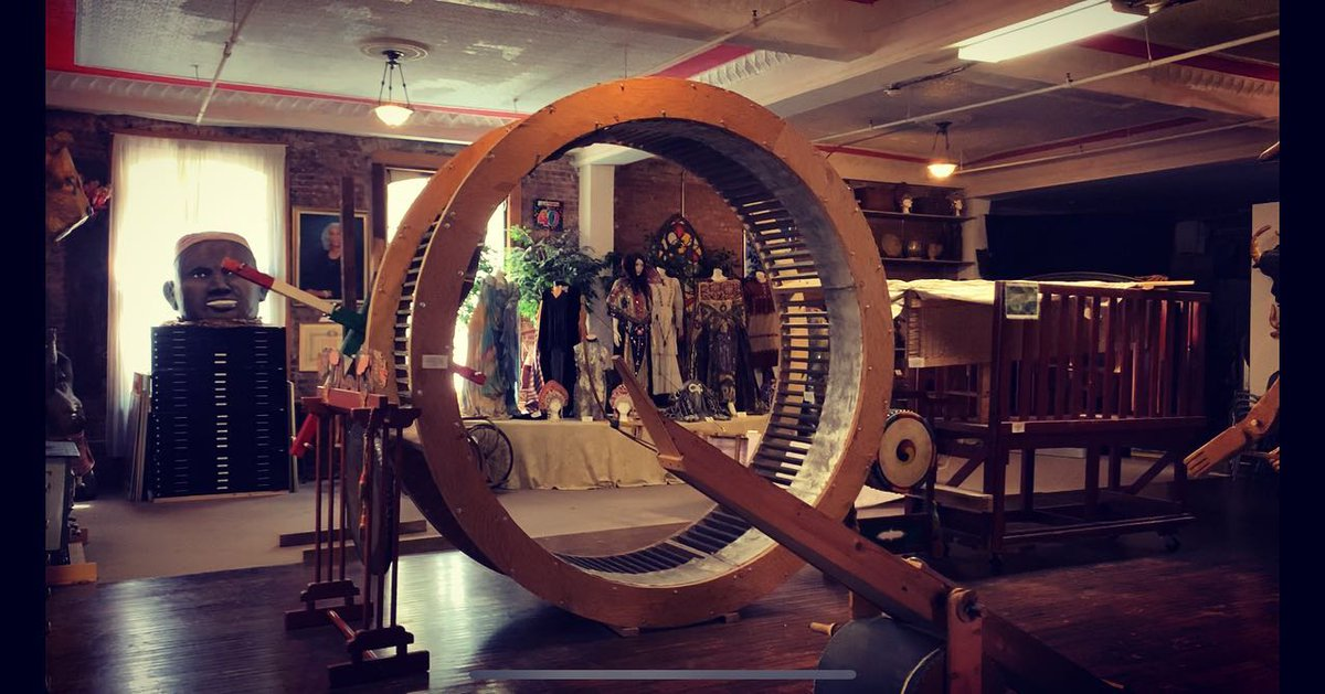 photo of the la mama archive with wood floors and windows and a giant wooden wheel in the center with other archival props