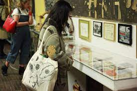 A woman looks at la mama archive items in a glass display case with her back to the camera