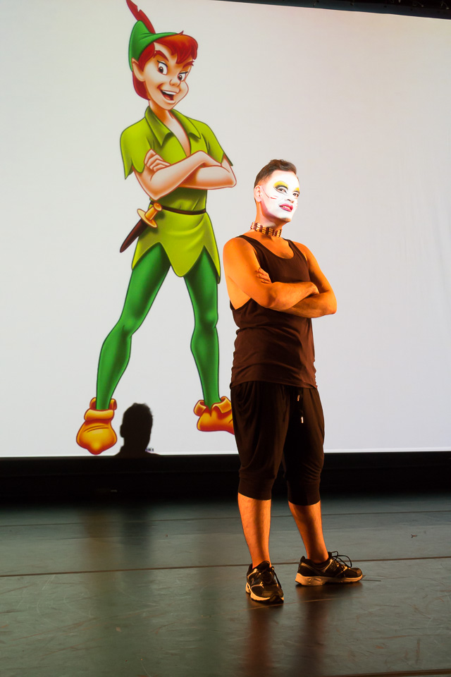 native american performer stands in white face with peter pan projected on wall behind him