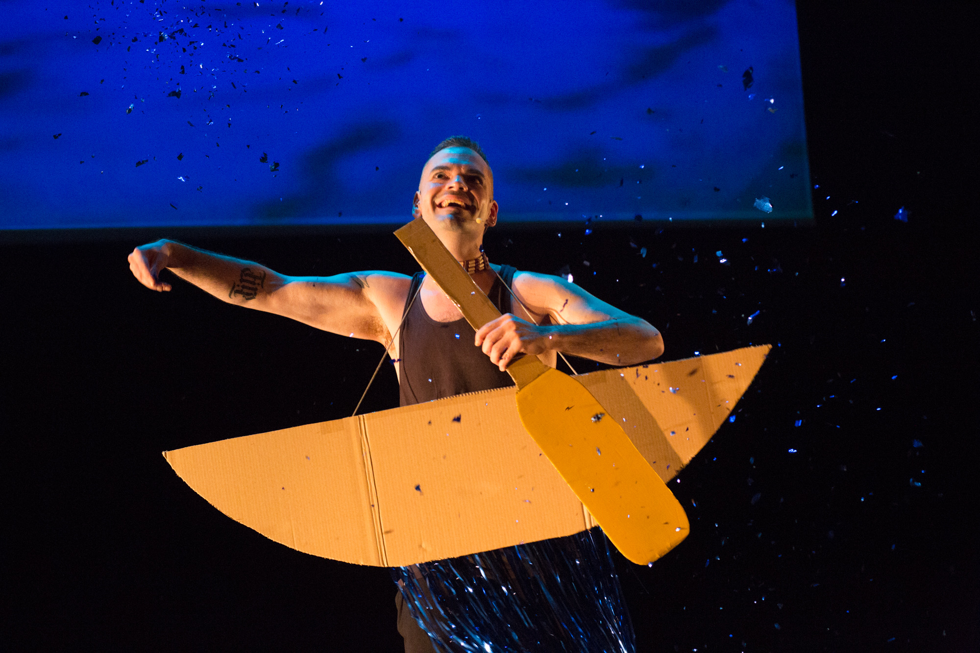 actor performing at la mama with a boat and paddle prop with a blue background