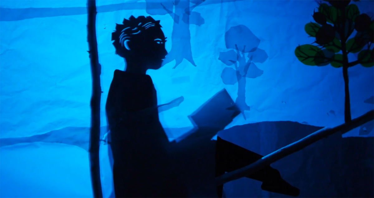 a dark shadow puppet sits with a book open in front of a blue wall