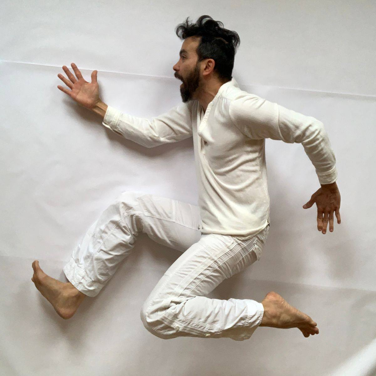 tom lee dressed in all white against a white background jumps in the air in a theatrical formation