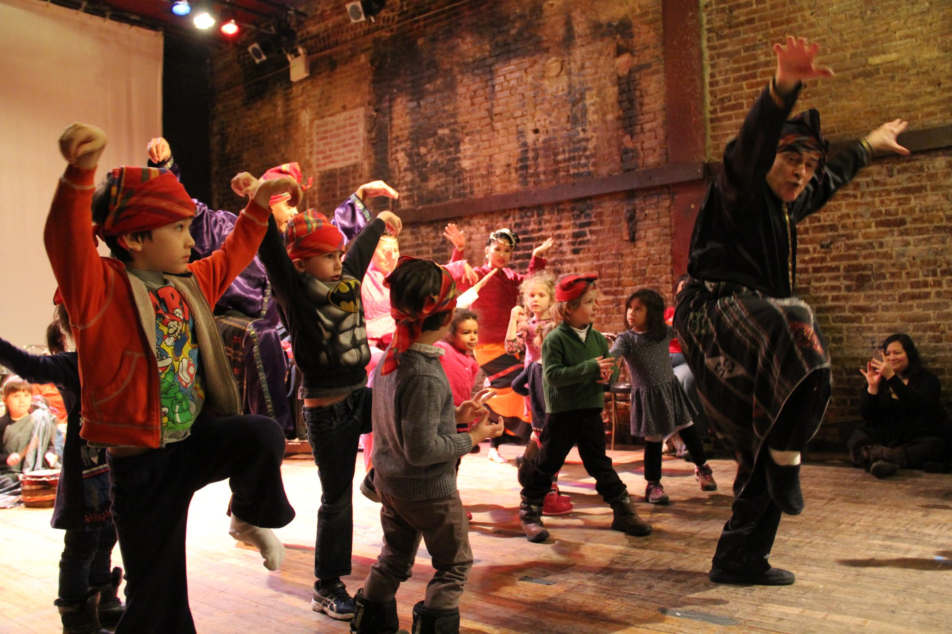 a dancer stands in front of a line of kids leading them in a la mama kids workshop