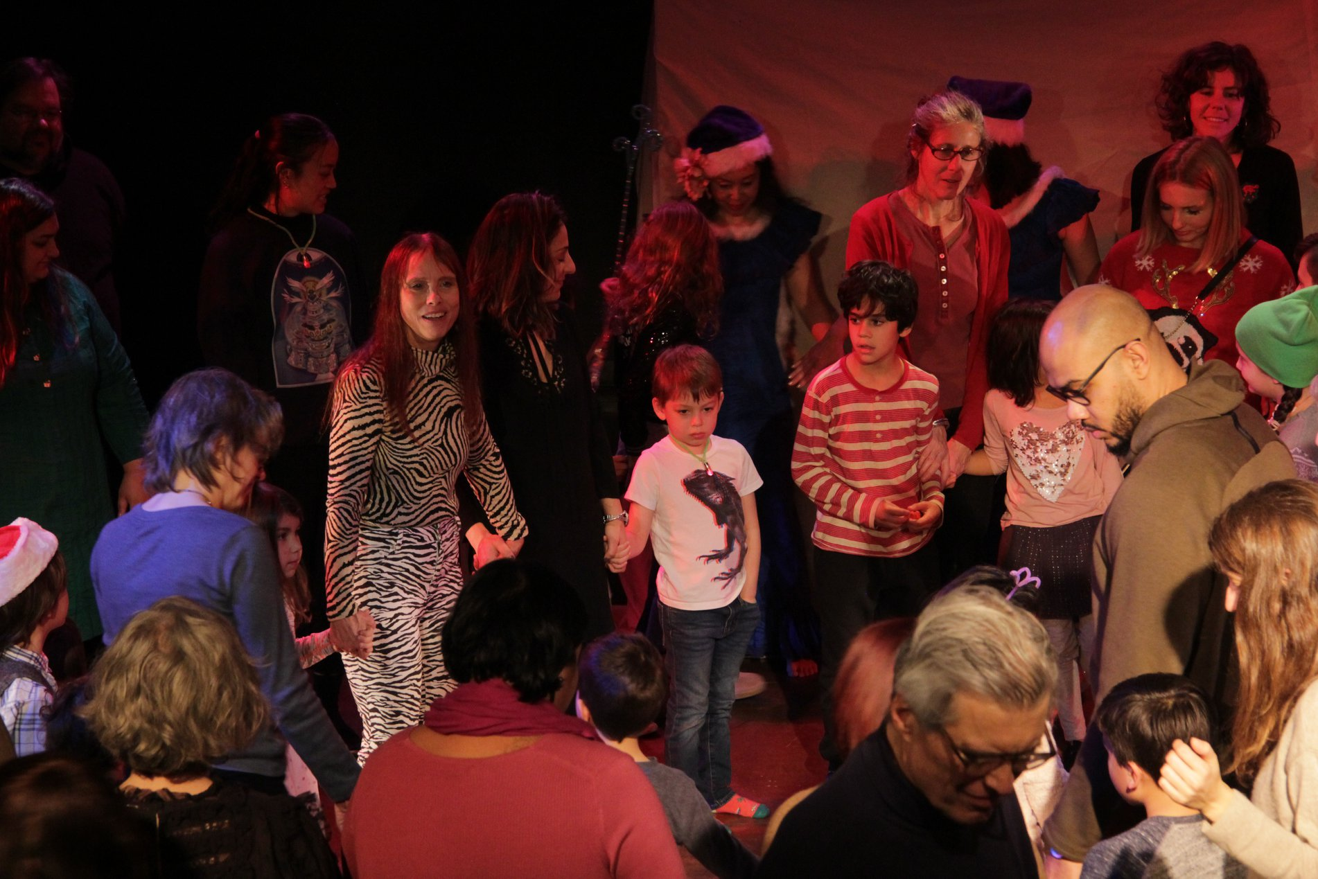 a crowd of families are bathed in soft red light during a la mama kids event