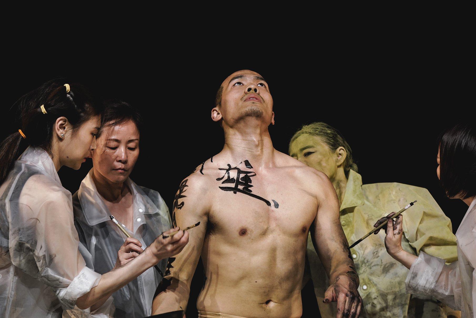 three women paint an asian mans body using ink