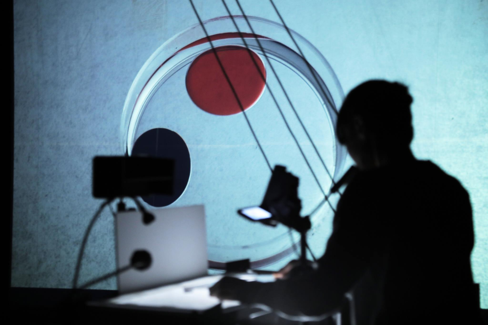 performer sits in silhouette with back to the audience manipulating small objects on a table and the image on a projector screen shows a tiny orange dot being moved