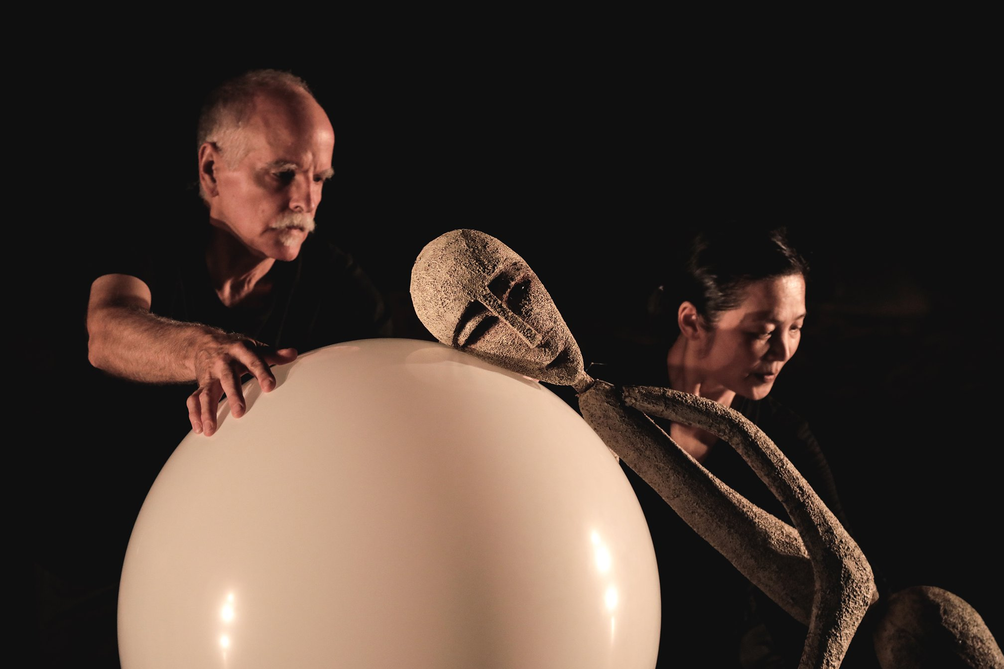 two performers manipulate a stick thin puppet leaning on a white ball in a dramatic pose