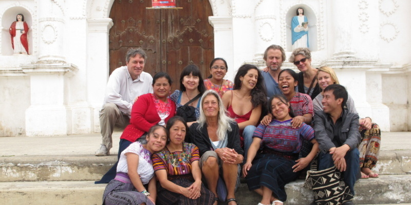 Members of the Trojan Women Project sitting on stairs outside in Guatemala