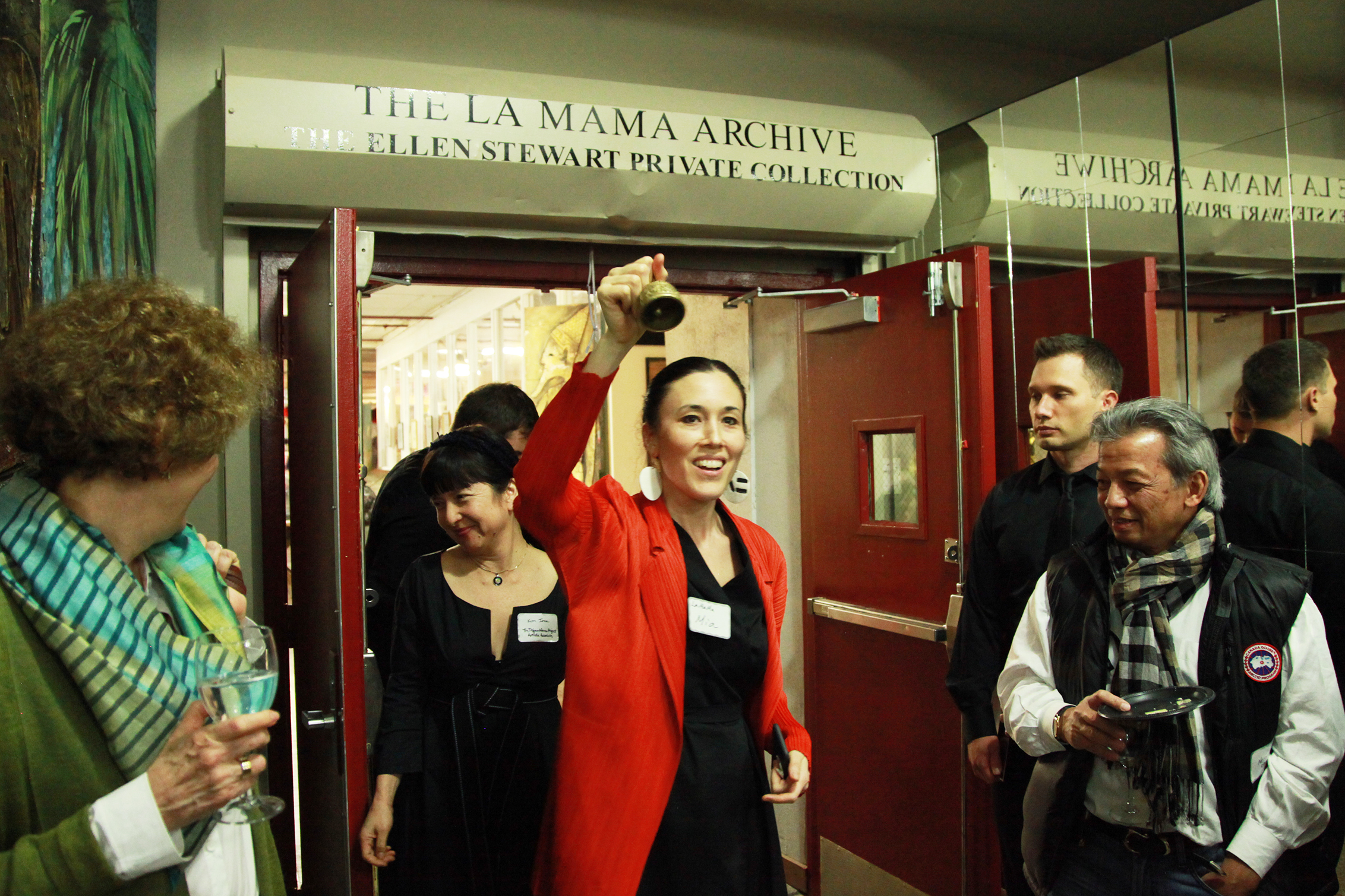 Artistic Director Mia Yoo ringing a bell at a Trojan Women Project event in a red jacket and black shirt
