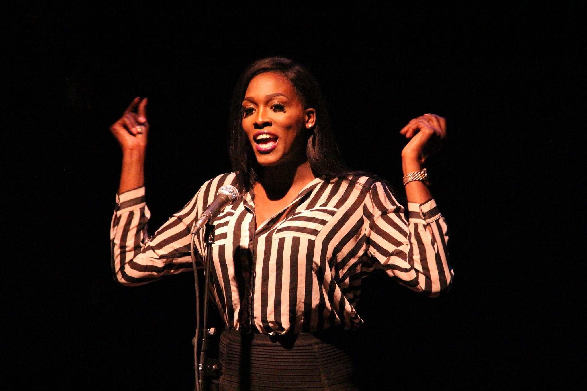 A performer in a black and white striped jacket snaps her fingers on stage at La MaMa's Squirts