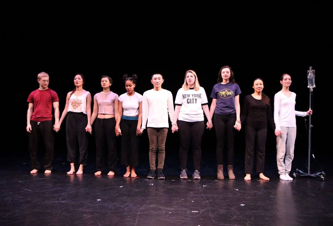 Trinity La MaMa students posing in a group on stage