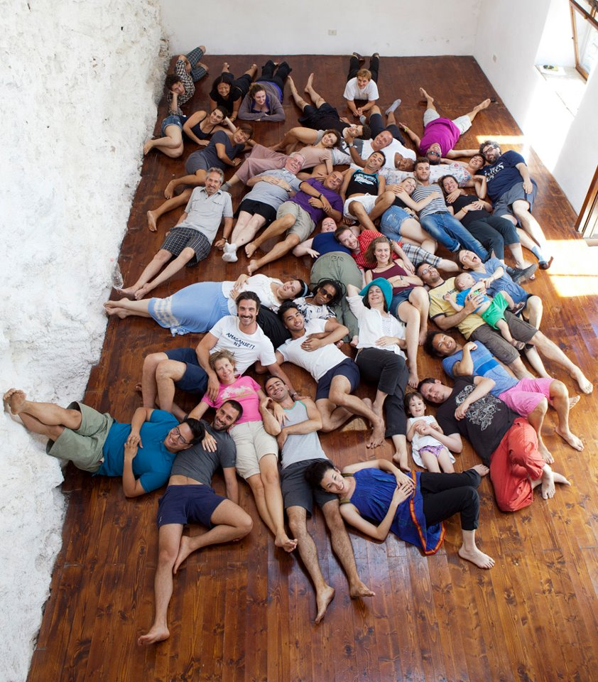 artists sit outside at La MaMa Umbria International posing on their backs for a camera above them