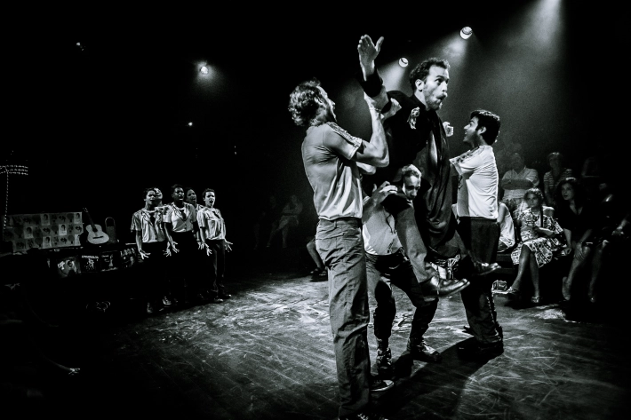 Black and white photo of people singing in the background and one man leaping while other men hold him