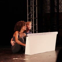 two people crouching behind a white wall onstage