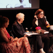 three people sitting onstage, one woman holding a microphone