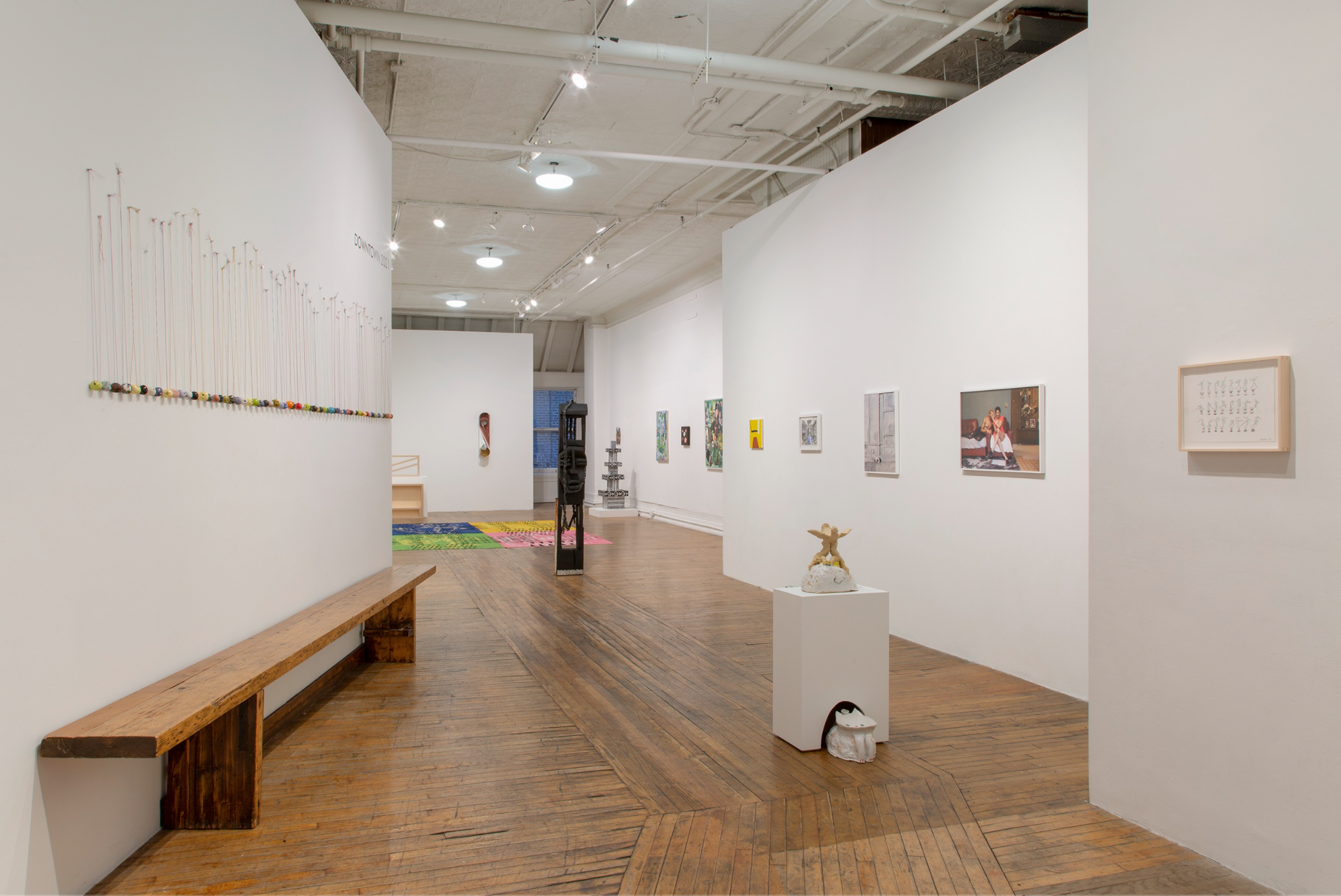 photo of gallery space with white walls and a wooden bench on the left wall